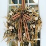 Ein Kranz aus saisonalem Blattwerk in herbstlichen Farbtönen garantiert einen warmen Empfang.